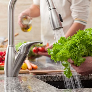 washing fresh lettuce under a faucet