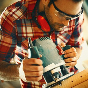Man using a power tool wearing safety glasses