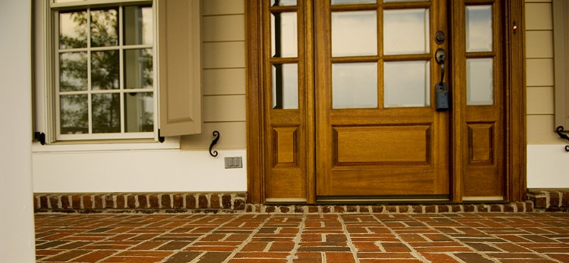 close up of a brick front porch with a front door and side window