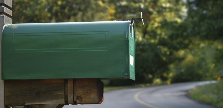 A green mailbox in a rural neighborhood.