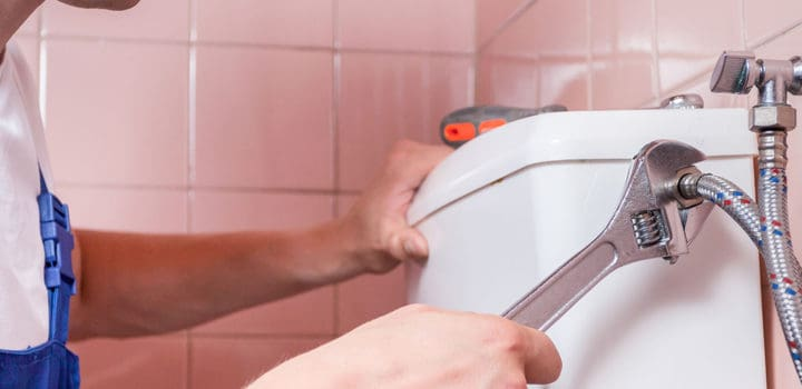 Plumber repairing a toilet pipe with a wrench