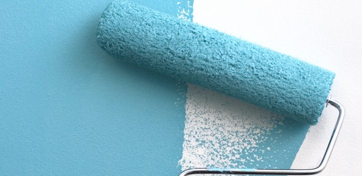 A paint roller covered in teal blue paint, painting over an interior white wall.