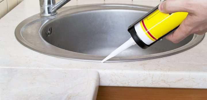 plumber using caulk around a kitchen sink