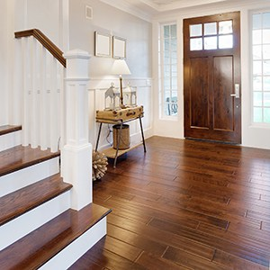 hardwood flooring in an entry way with a craftsman style door and a hardwood staircase