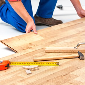 a man installing flooring using a variety of tools including a tape measure, spacers, a mallet and tapping block