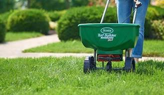 a person spreading lawn fertilizer on grass with a lawn spreader
