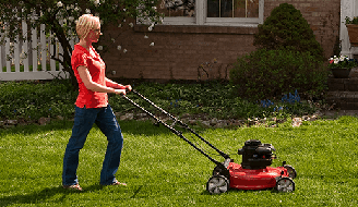 woman in a red shirt and jeans mowing grass