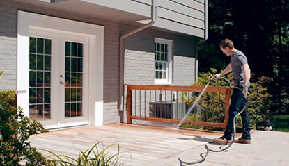 man cleaning deck with hose before applying deck stain