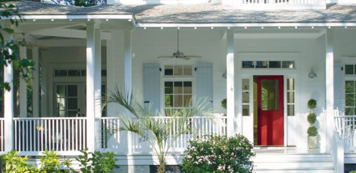 white house with a large farmer's porch and a bright red front door