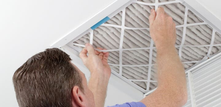 a man changing a ceiling air filter for his furnace